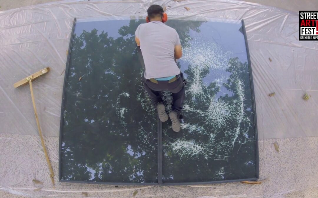 Street artist makes portraits by hitting windows with hammers
